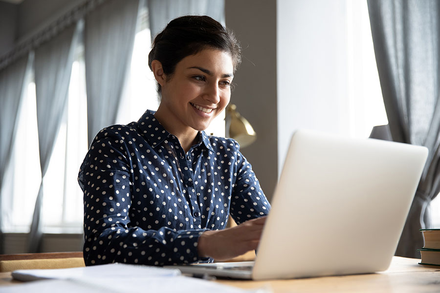 A woman smiling whilst looking at a mac computer