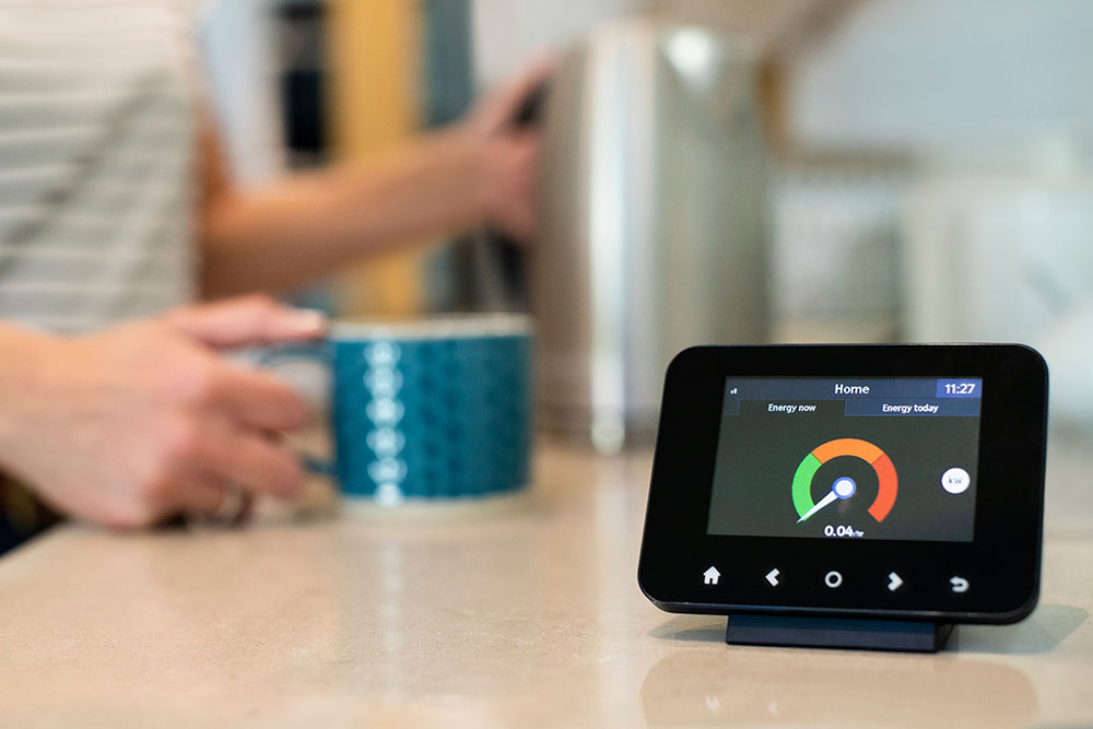 A smart meter with a man's arm holding a cup of tea in the background