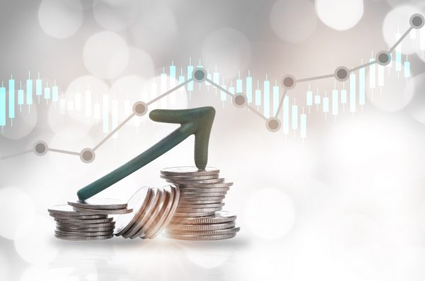 Green arrow upward on stack of coins and growth graph on bokeh background
